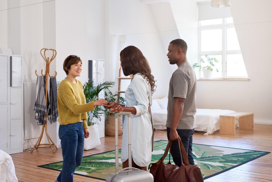 Wohnsharing: Frau begrüßt Paar in ihrer Wohnung
